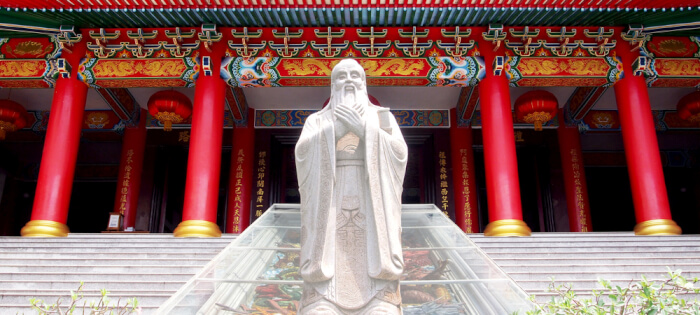 Confucius statue in front of traditional  Chinese historic architecture